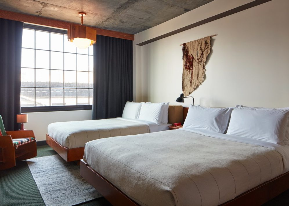 Room with two queen size beds and white sheets, a big window, decoration on the wall