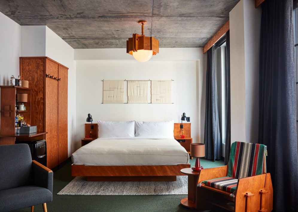 Room with a king size bed and white sheets, teak chair, shelves, big windows with dark blue curtains