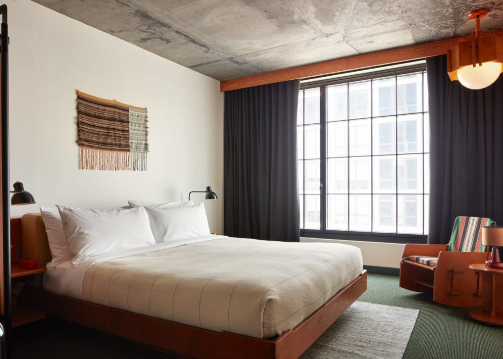 Room with a queen size bed and white linen sheets, decoration on the wall, an armchair, a big window