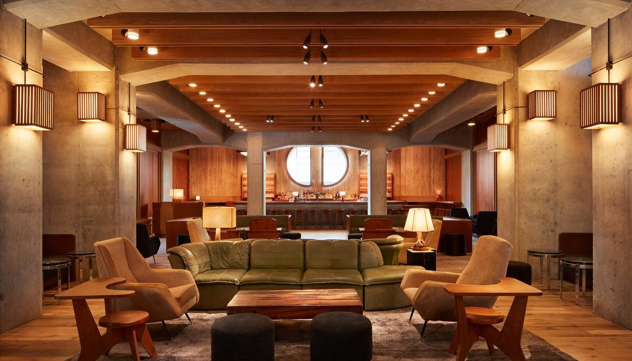 Spacious lobby at ace hotel with a leather sofa, armchairs, coffee table, wooden ceiling and lights, a bar in the background