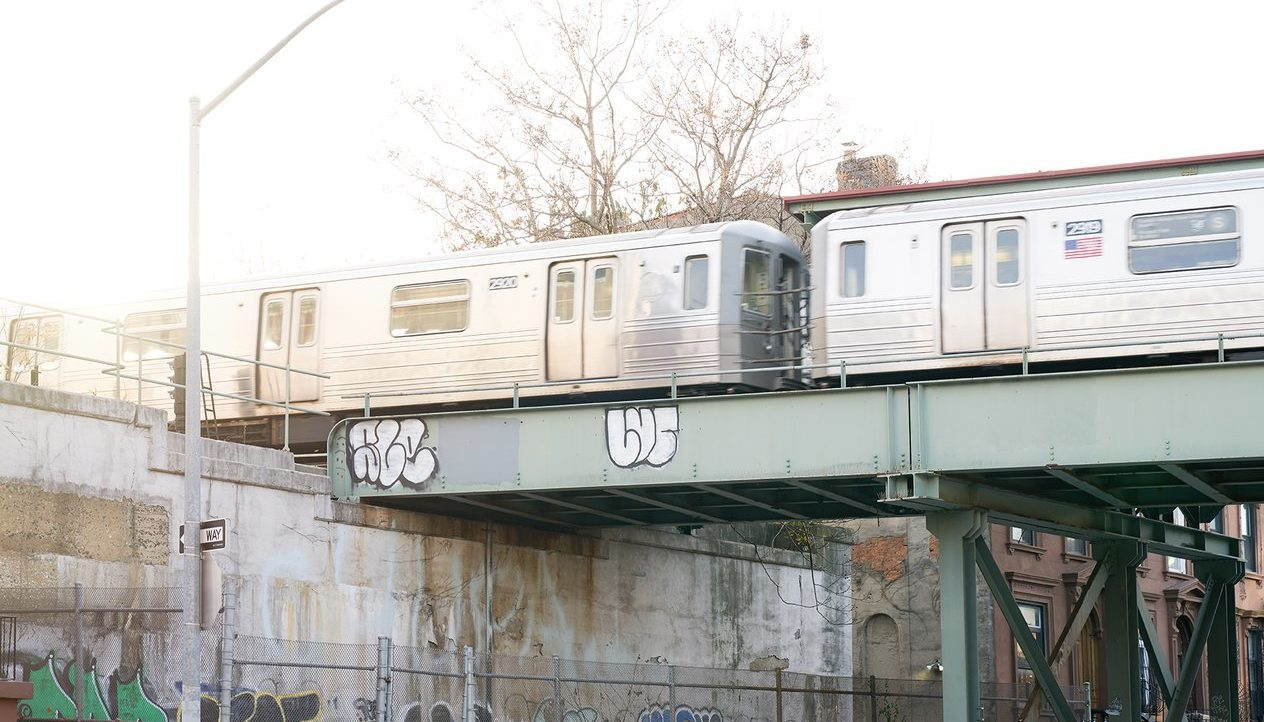 Two subway trains crossing the bridge during daytime