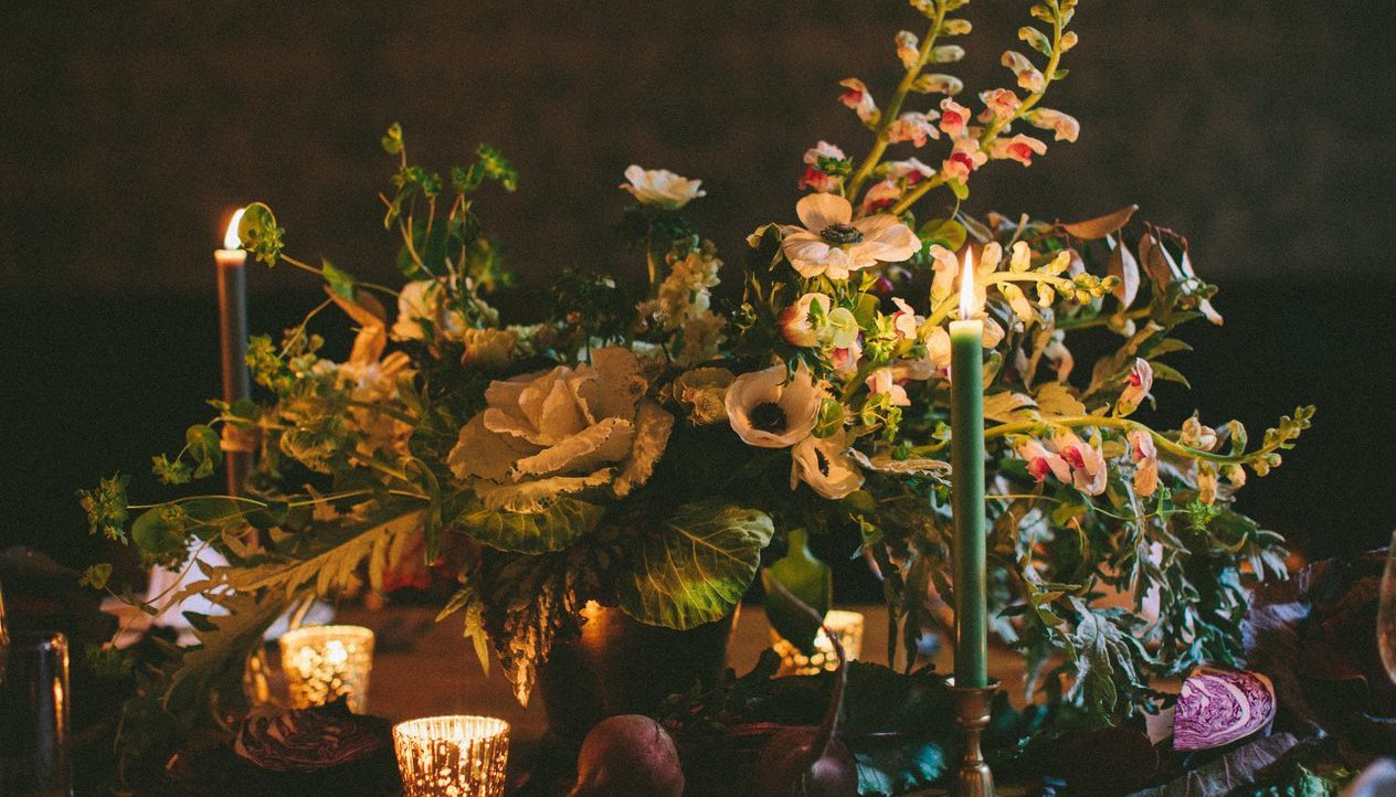 A flower bouquet and candles on the table