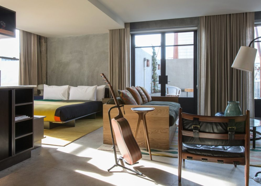 A hotel room with a bed, seating area, kitchenette and guitar