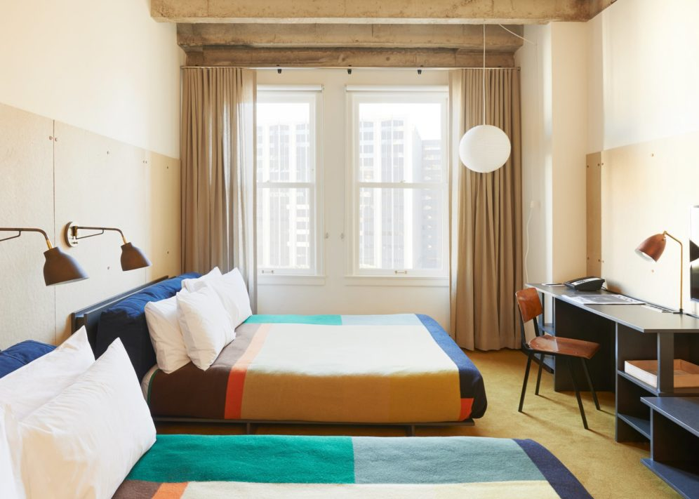 A brightly lit hotel room with two queen beds and a desk