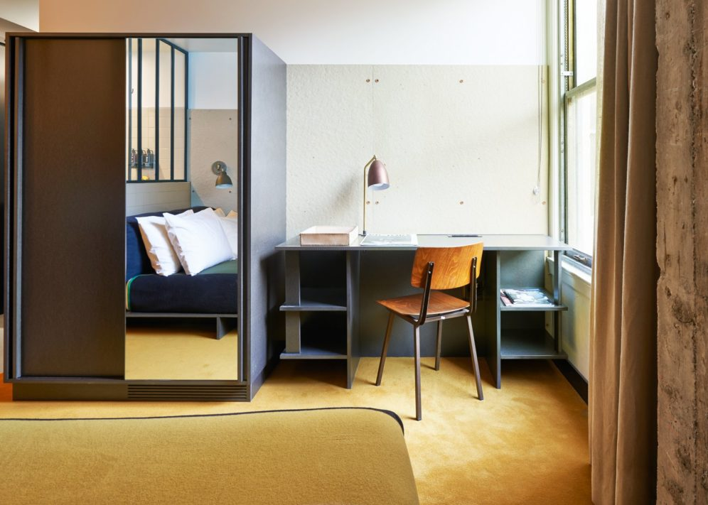 A hotel room with a desk and closet