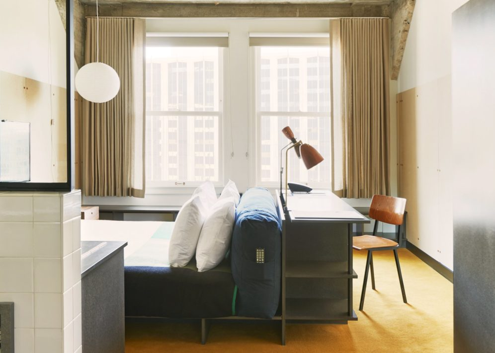 A brightly lit hotel room with a bed and desk