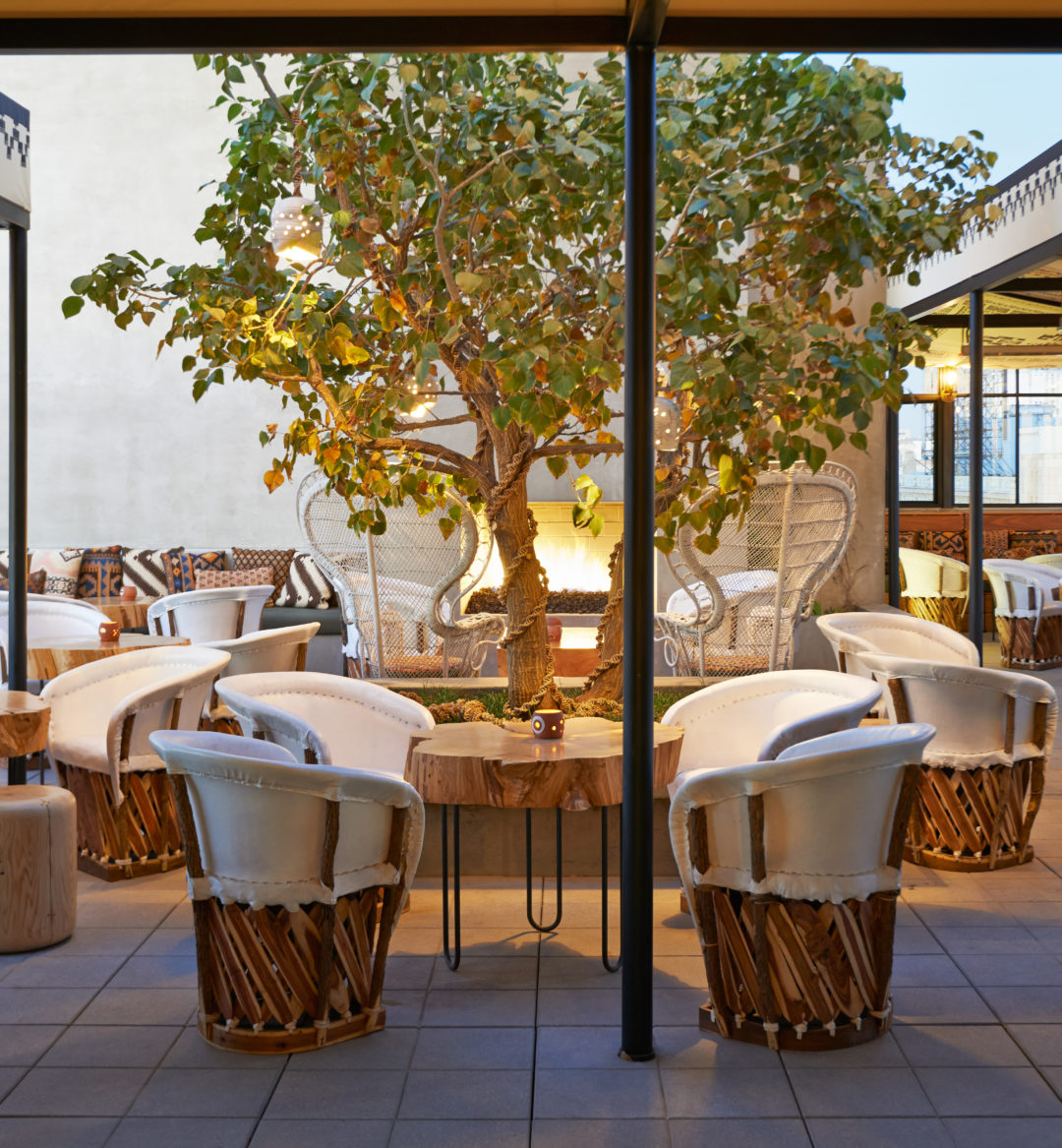Patio with tables and chairs surrounding a tree