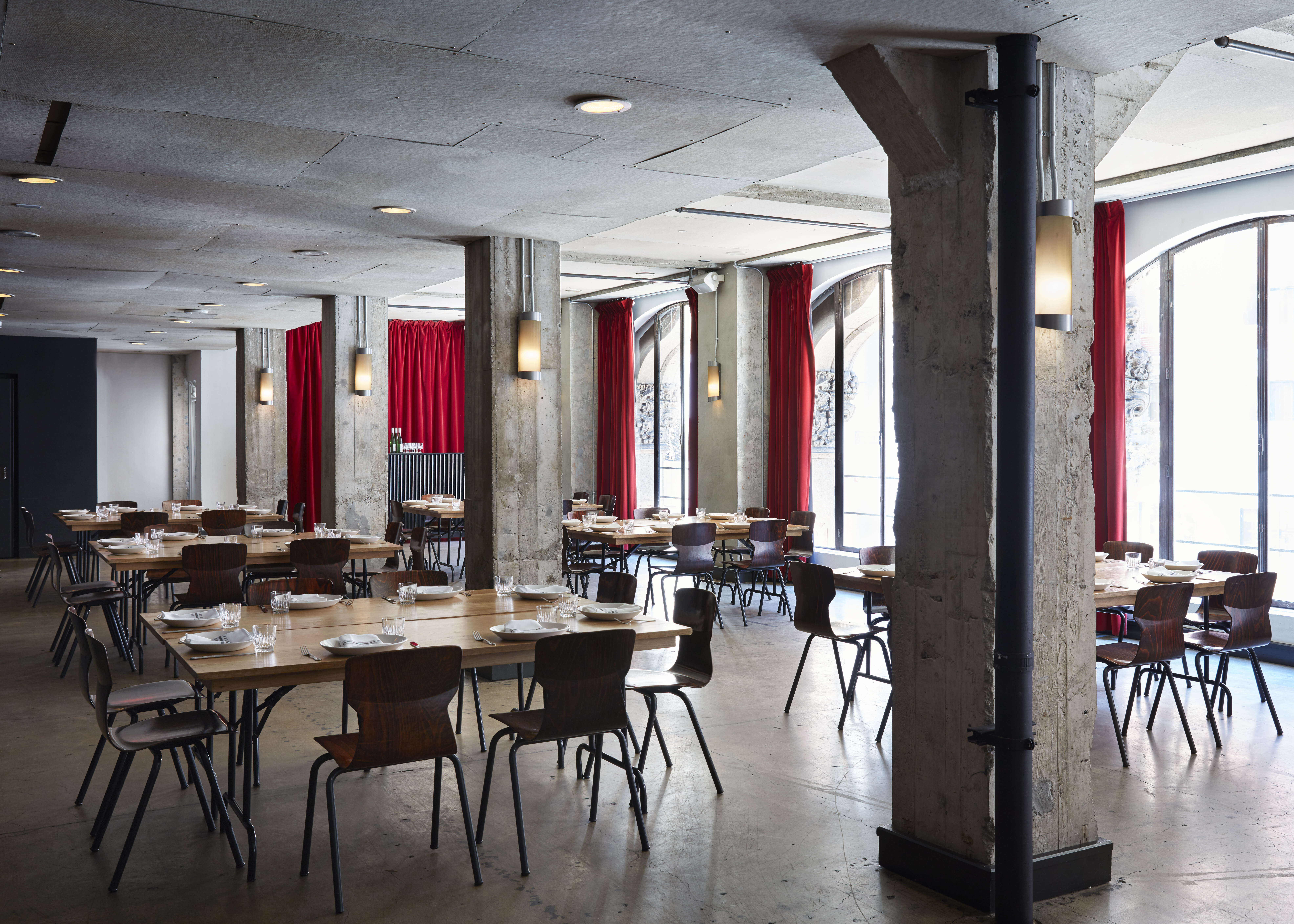 Restaurant with large tables, cement beams and red drapes