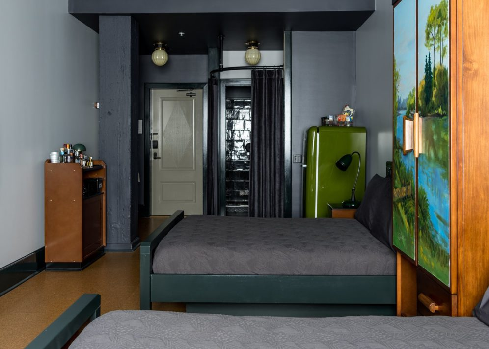 A hotel room with two double beds, bathroom and refrigerator