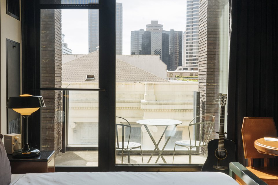 A hotel room patio with seating area and view of the city