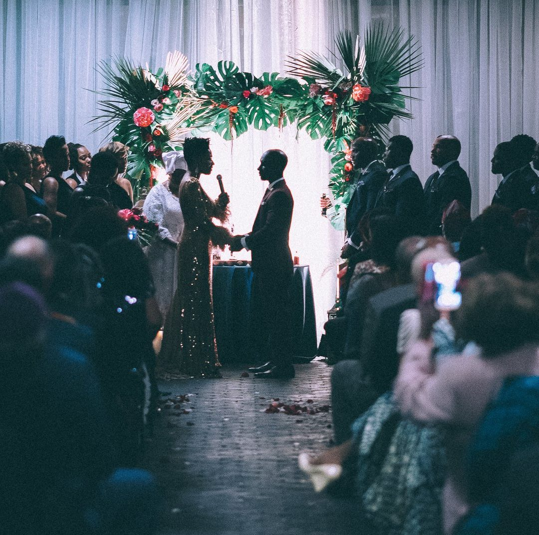 A couple exchanging wedding vows in front of many guests
