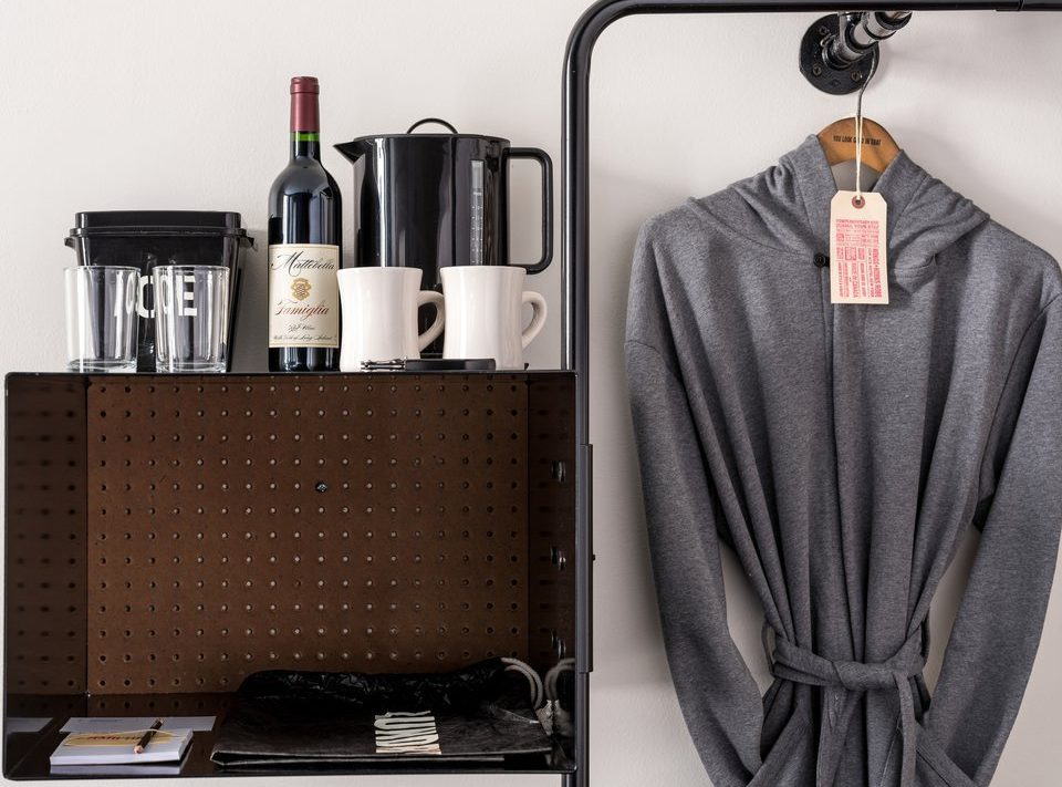 Hotel amenities including a coffee maker, bottle of wine and a bathrobe