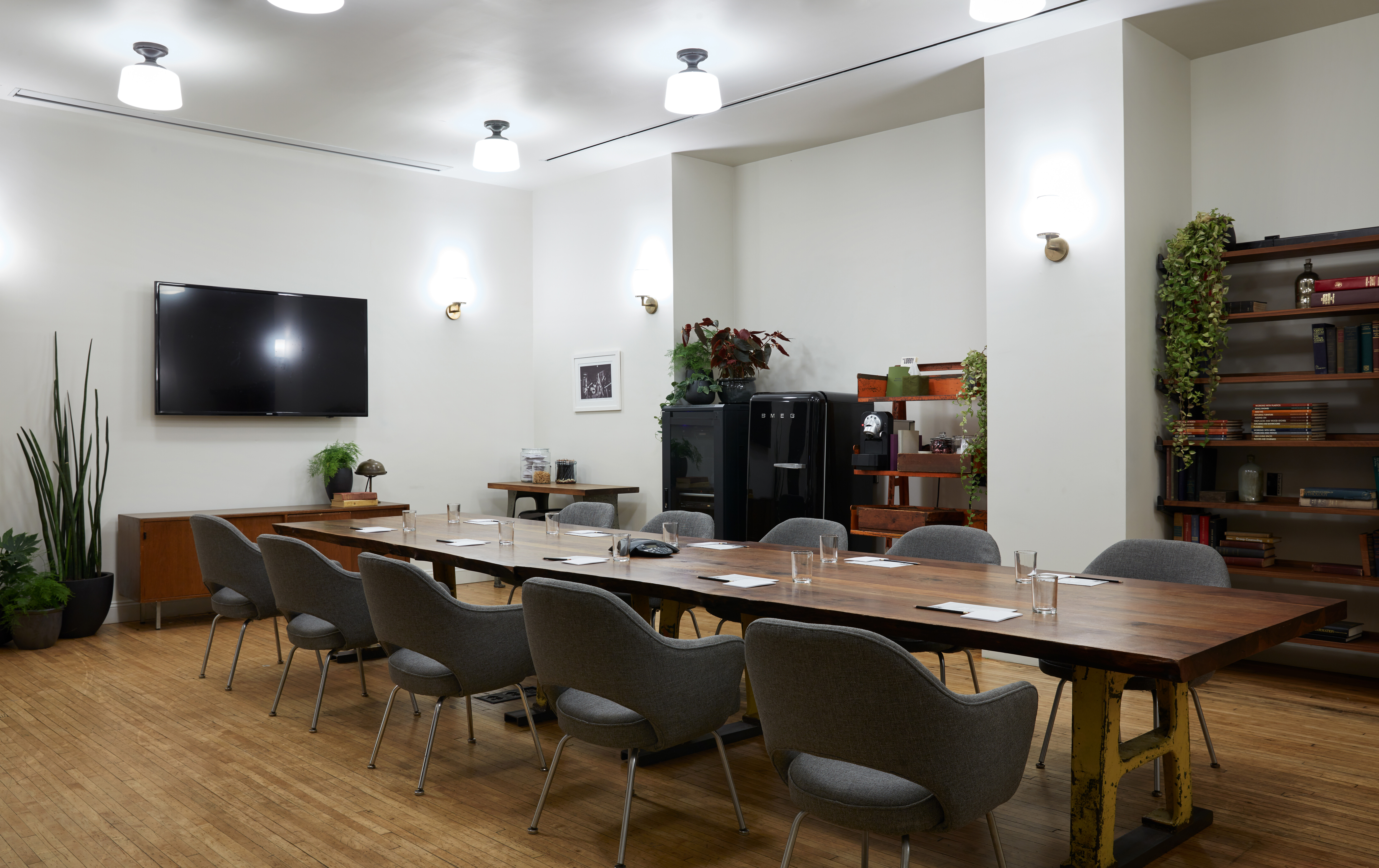 A meeting room with a large table and a TV