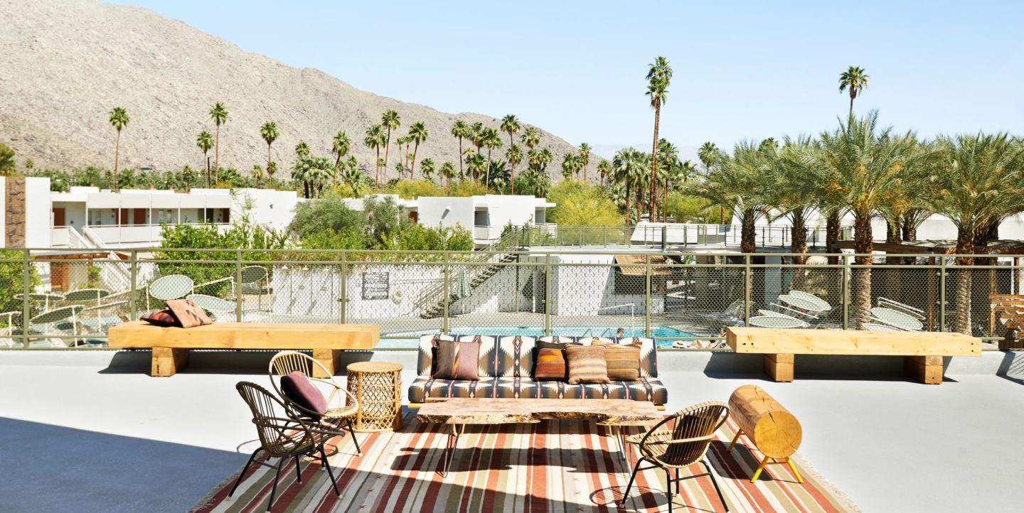 A outdoor poolside sitting area with patterned couch, rug, and table and chairs