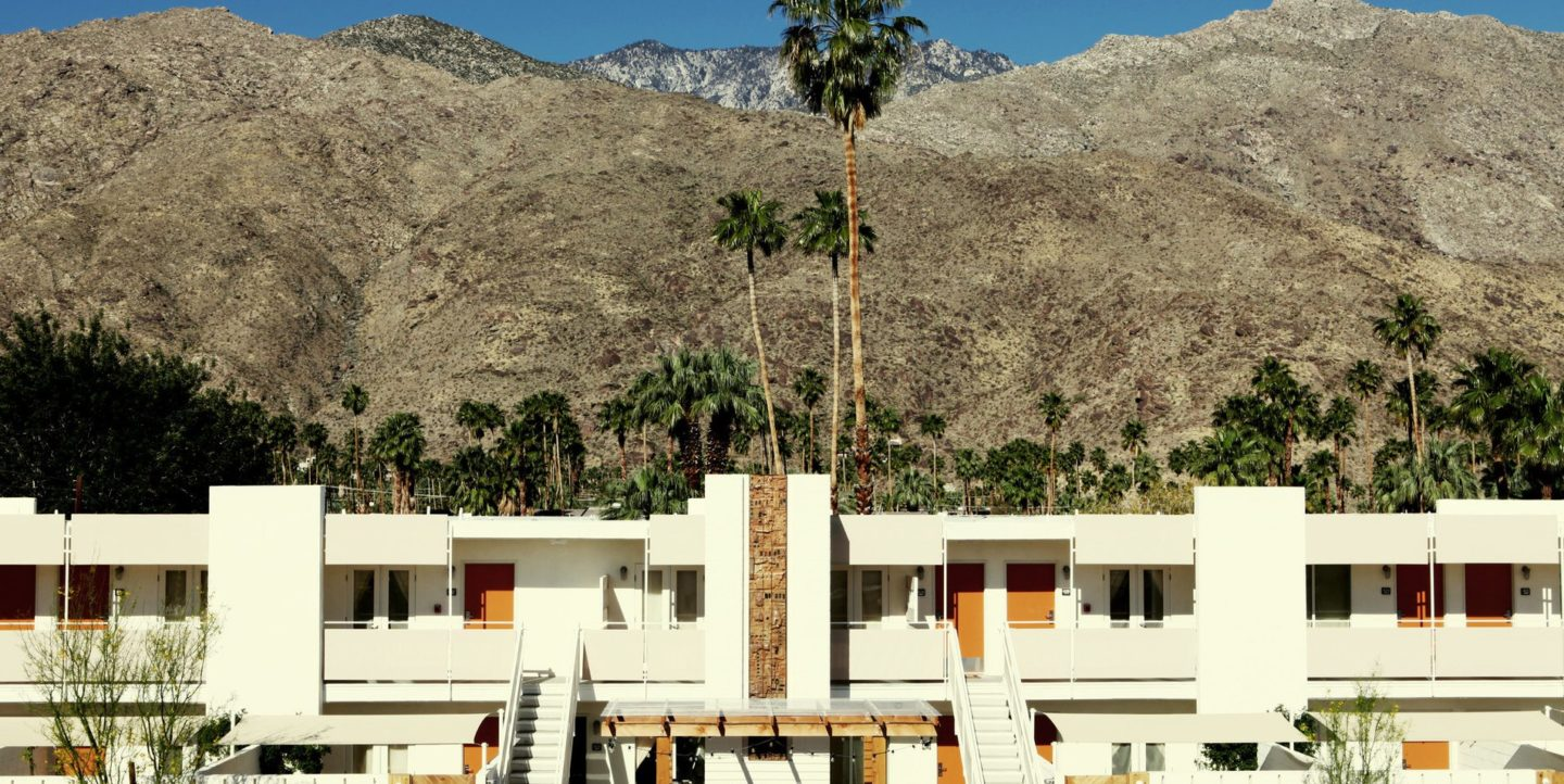 Outside view of Ace Hotel with a view of mountains and palm trees behind