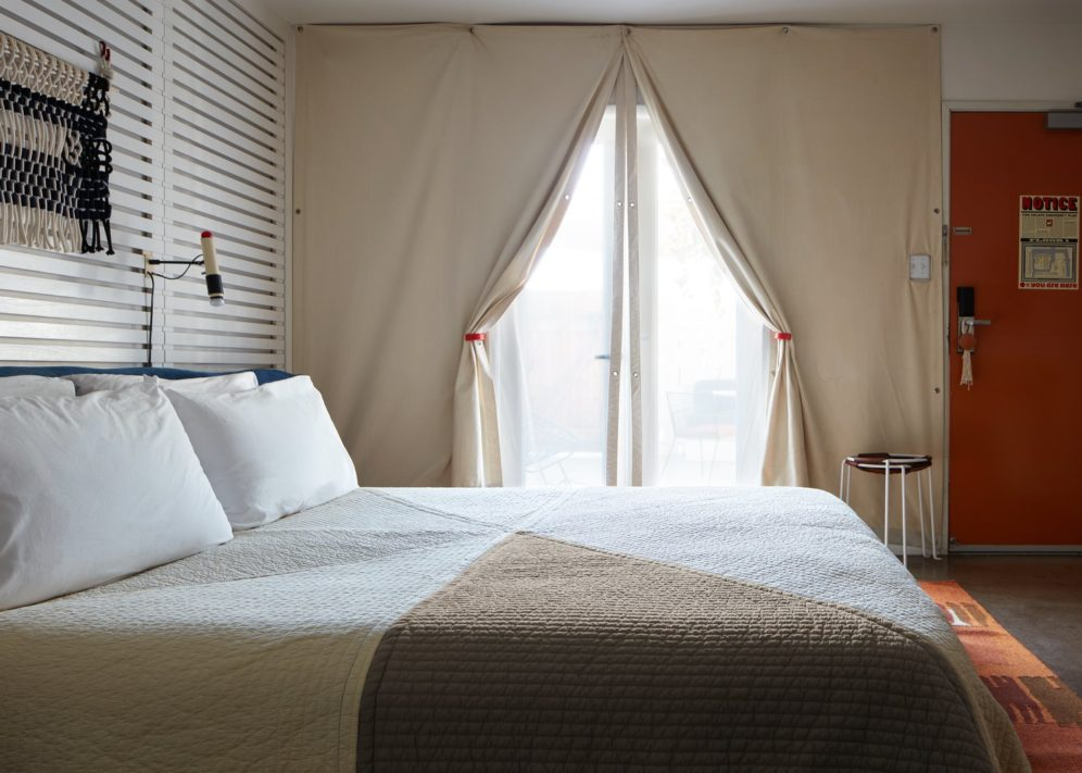 A hotel room with a large bed by patio doors