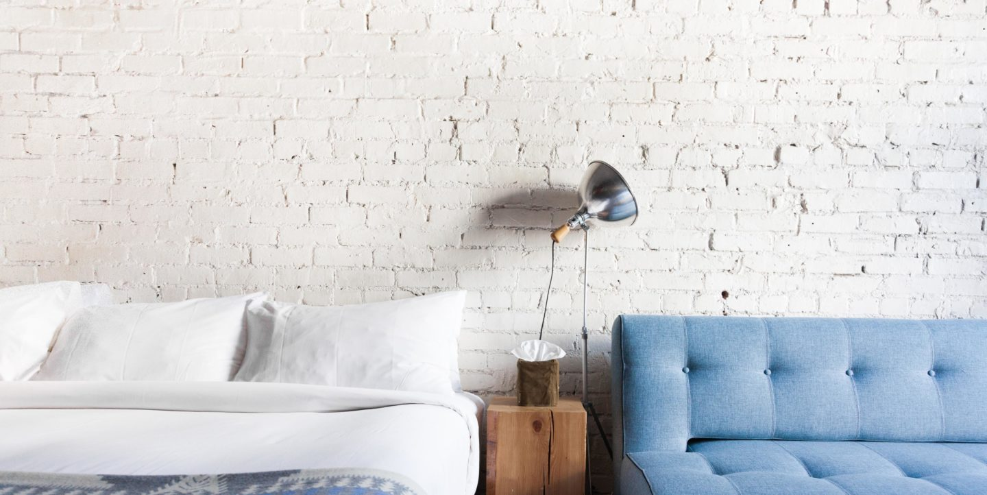 A hotel room with a bed and couch against a white brick wall