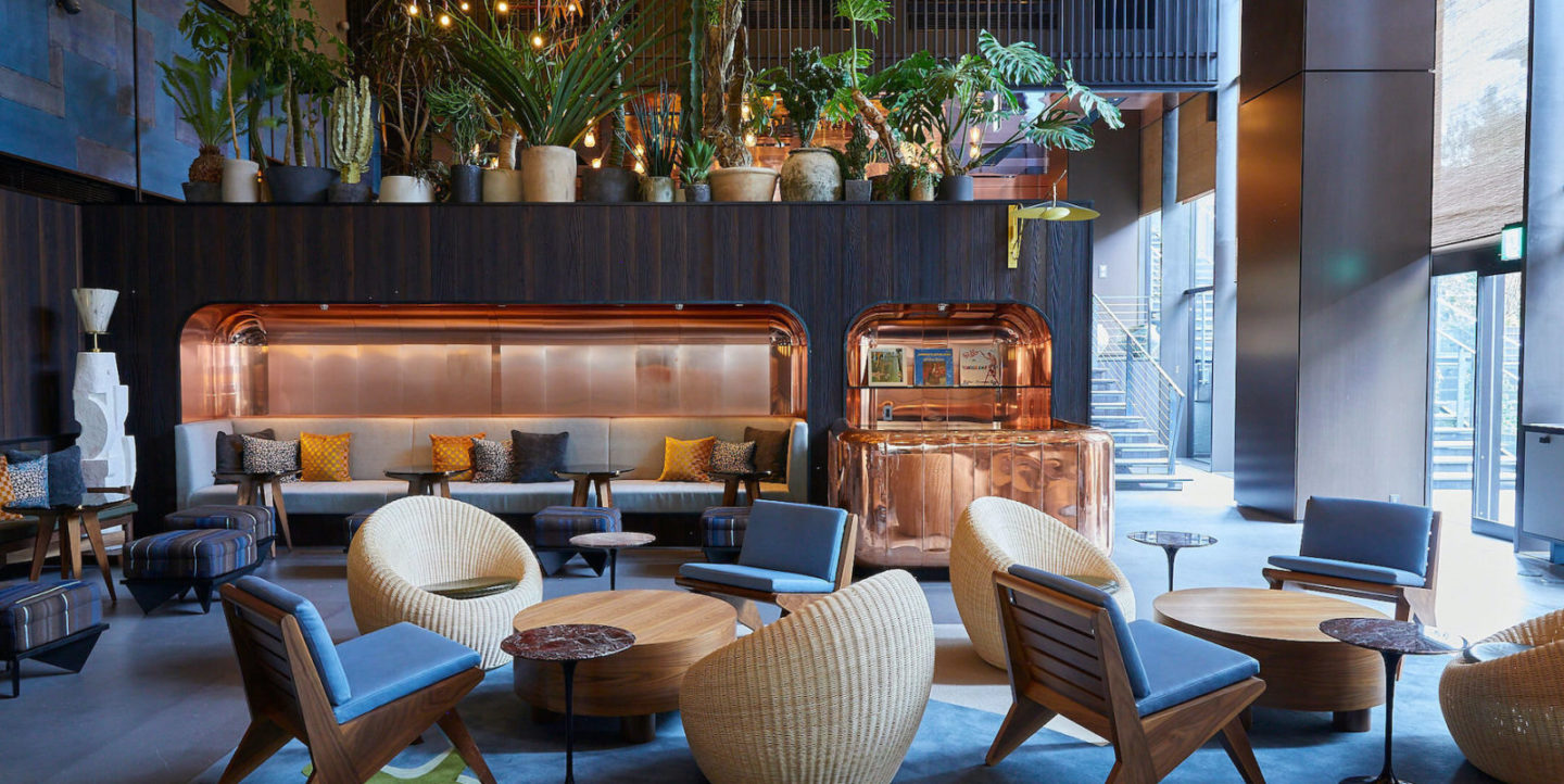 The lobby of the Ace Hotel with blue chairs and basket chairs