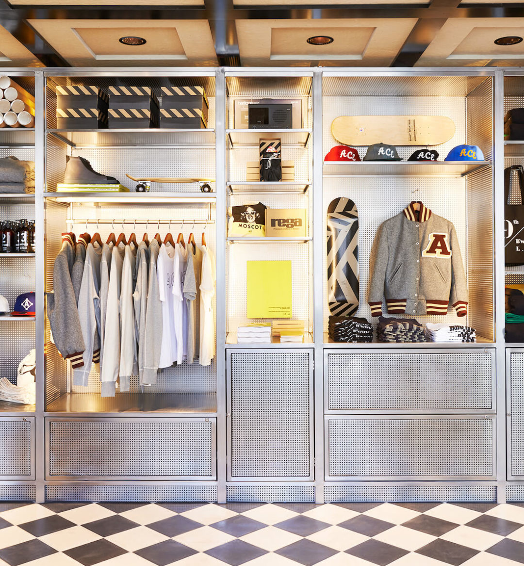 A closet with t-shirts, jacket, hats, shoes and board.