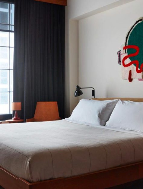 Queen size bed in a bright room, a green decoration on the wall